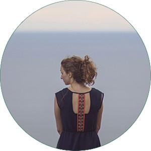 Sitzende Frau von hinten, im Hintergrund der Horizont