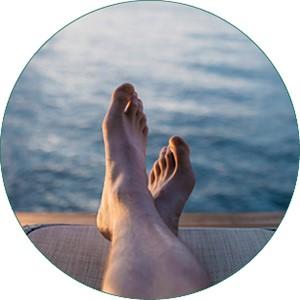 Füße sind übereinander geschlagen auf einem Steg