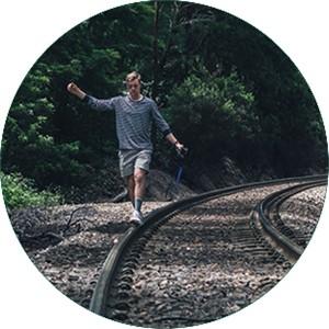 Mensch balanciert über Bahngleise