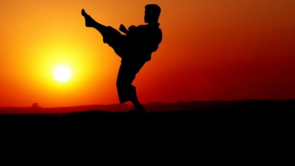 vor orangenem Sonnenuntergang ist ein Mensch in Kämpferpostion, zeigt seine Stärken